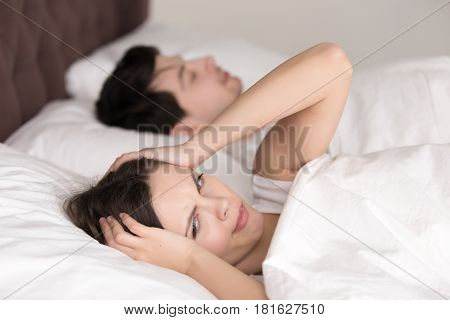 Annoyed upset wife trying to sleep with snoring husband asleep next to her, young girl waking up with headache, can not sleep, having insomnia, feeling bad in the morning after sleepless night