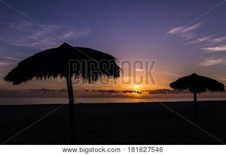 Beach parasols seen on the coast of Cayo Coco at sunrise.