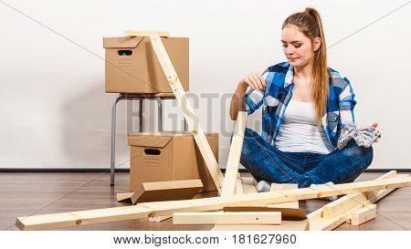 Woman Moving In Holding Screws And Furniture Parts
