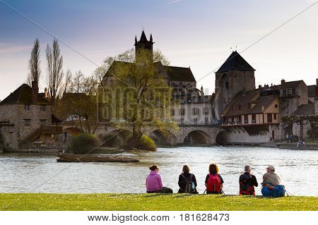 Moret-sur-Loing France - March 26 2017: Group of tourists sitting near Loing river. This town was a source of inspiration for Monet Renoir and Sisley. French culture and travel destinations concept.