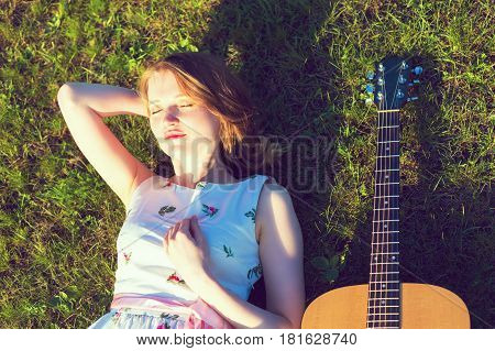 Young Woman Lying On Back In The Sun With Guitar On Green Grass. Toned Photo