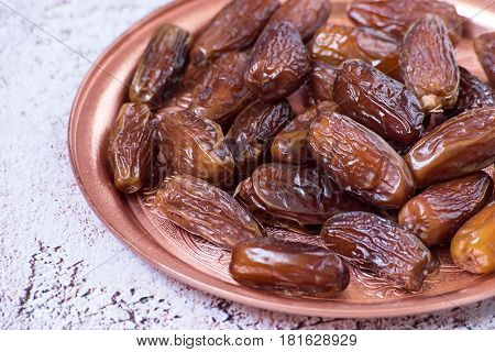 Useful food. Dried sweet dates on a round copper tray.