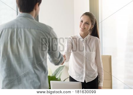 HR manager meeting with job applicant at the office for interview, two smiling business partners making agreement, greeting, handshaking, shaking hands before negotiations. Welcome to our team concept