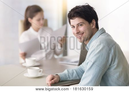 Happy young man looking at camera, sitting at the office desk while female manager checking papers in the background. Successful job interview, business incubator, startup promotion, taking out loan