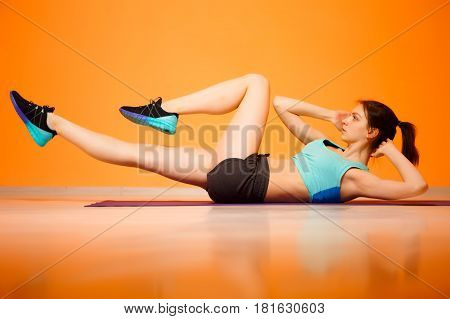 Young girl doing exercises on press in gym