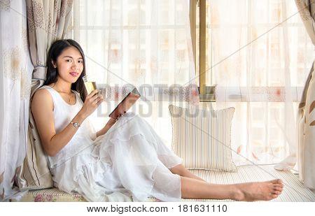 Girl Having Tea By A Bay Window