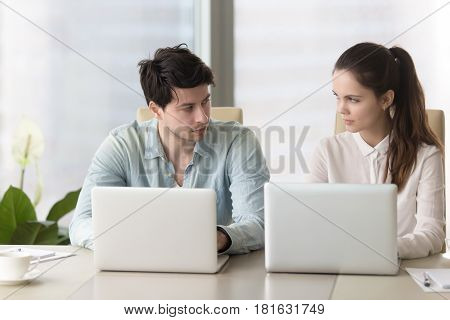 Competition and rivalry between office workers. Male and female colleagues sitting together at conference table using laptops looking in the eye, dislike each other, feeling jealous, being envious