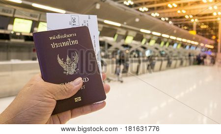 Tourist hold passport and boarding pass at the counter for check-in and travel in the airport. Passport and boarding pass for travel concept.