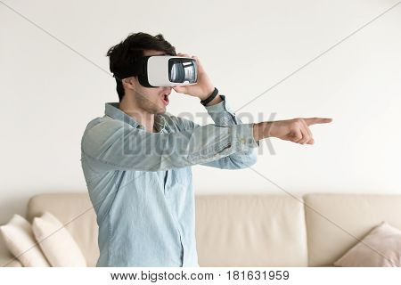 Surprised man using VR headset pointing at objects in augmented reality, wondering helmet innovative abilities, amazed young guy enjoying playing virtual games, watching 360 degree videos