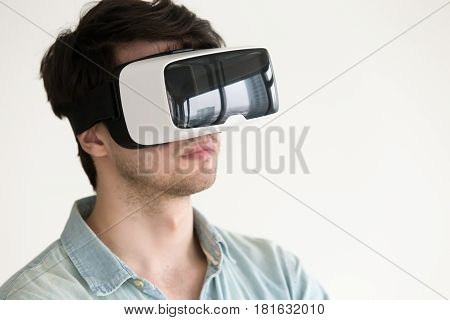 Portrait of serious young man testing 3d virtual reality headset for studying and entertainment, immersing into visual world, travel experience using apps for vr simulator, watching 360 degrees video