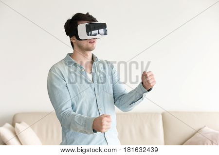 Playing vr games or using applications. Young gamer in wearable VR headset playing action video games with realistic graphics at home. Virtual gaming concept, experiencing augmented reality