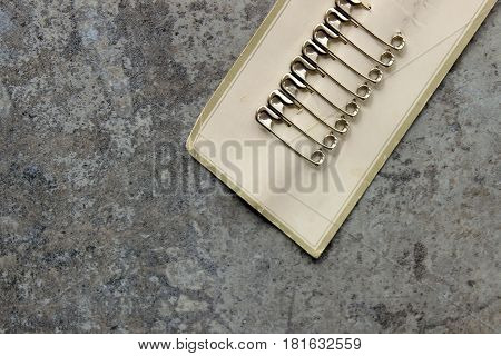 Vintage safety pins on retro card. Copy space.
