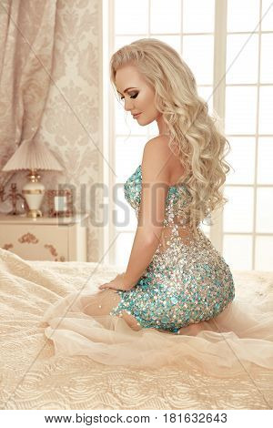 Beautiful Sensual Blond Bride Woman With Makeup And Long Curly Hair Style, Posing In Luxurious Dress