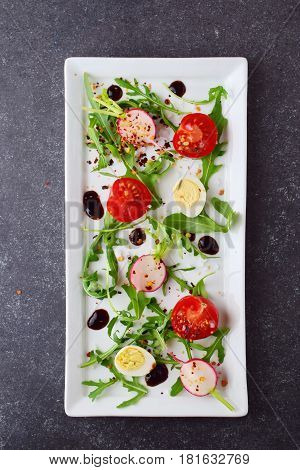 Fresh radish, cherry tomato, quail egg, ruccola with balsamic glaze on a white plate. Mediterranean lifestyle. Healthy food.