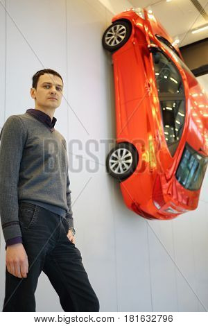 MOSCOW - APR 16, 2016: Hyundai Solaris on wall and man (with model release) in Hyundai Motorstudio. Hyundai produces not only cars, but also its own collection of furniture and household items