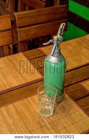 Green vintage retro soda siphon on wooden table