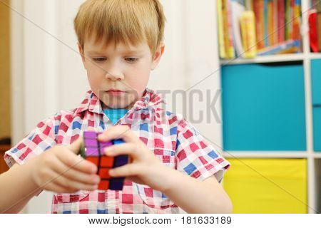 MOSCOW - MAY 7, 2016: Boy (with MR) plays with Rubik Cube. Over 350 million cubes sold worldwide making it world top-selling puzzle game and the world best-selling toy