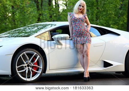 MOSCOW - MAY 20, 2016: Beautiful woman (with MR) pose near at Lamborghini Huracan LP 610-4 outdoor. Lamborghini Huracan is world first production car, using inertial navigation system