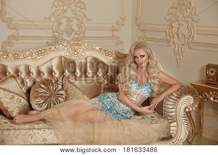 Beautiful Alluring Gorgeous Woman In Fashion Dress Lying On Modern Sofa With Frame In Luxury Interio