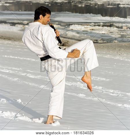 Man in white kimono is practicing barefoot martial arts in the snow.