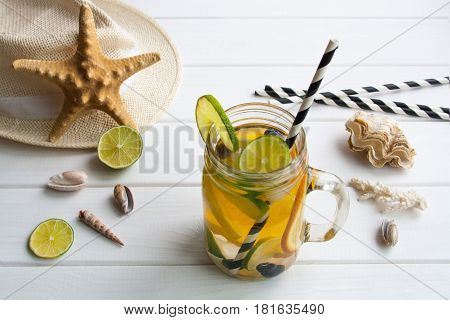 refreshing water with lime and orange on a white wooden table