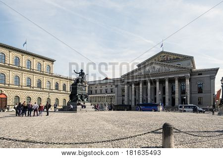 Munich-Bavaria-Germany. March 29 2017. View of the Bayerisches Nationaltheatere (National Theater of Bavaria) with people watching the statue of Max-Jospeh in his square