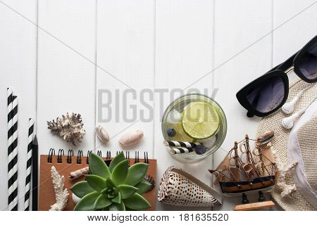 Flat lay. Drink with lime seashells on white wooden table. Summer travel concept
