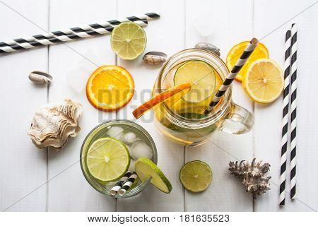 Flat lay. Orange and lime in a glass and jar a refreshing drink on a white wooden table