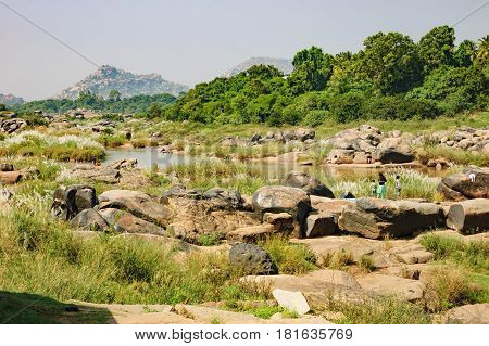 Hampi, India - November 20, 2012: Indian children in traditional clothes walking on the shore of the Tungabhadra River in Hampi India.