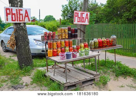 Selling pickles in village - many glass jars with mushrooms, vegetables in village, red text translation - fish, fish