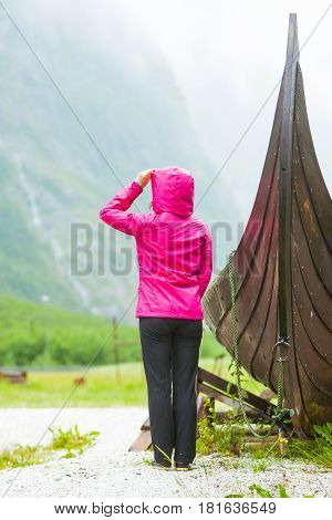 Tourist Standing Near Old Wooden Viking Boat In Norwegian Nature