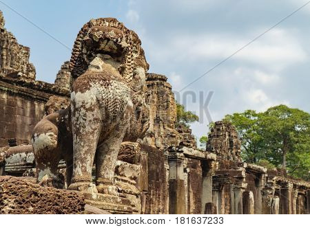 Lion in the foreground guards Prasat Bayon central temple of Angkor Thom, Siem Reap, Cambodia. Ancient Khmer architecture and famous Cambodian landmark, World Heritage.