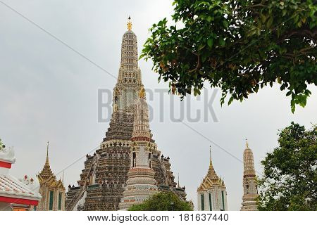 Stupa encrusted with coloured faience in Temple of Dawn Wat Arun, Bangkok, Thailand. Ancient Thai temple surrounded by tropical trees against the cloudy sky