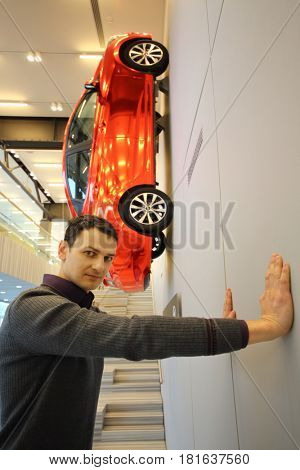 MOSCOW - APR 16, 2016: Hyundai Solaris on wall and man poses (with model release) in Hyundai Motorstudio. Hyundai produces not only cars, but also its own collection of furniture and household items