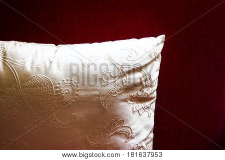 White Pillow Cushion On Dark Red Background. Decorative Luxurious Cushion With Ornament