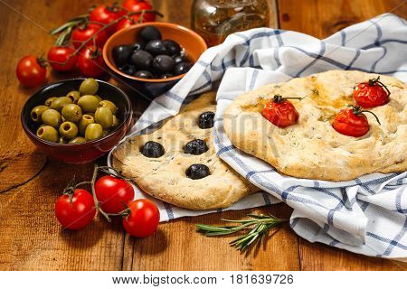 Traditional Italian Focaccia with tomatoes and olives and rosemary with olive oil on wooden table