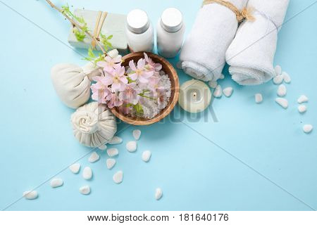 Spa concept on blue background with herbal ball, salt in bowl, candle , cherry ,towel