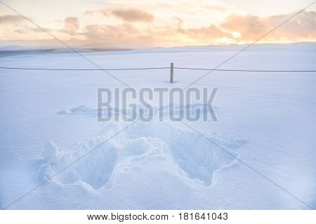 Snow print of human full body shaped on the thick fresh snow with sunset
