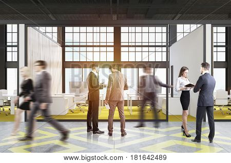 People in an office cubicle with a bright yellow floor white tables and computers on them in a loft. 3d rendering.