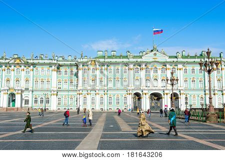 April 13 2015 - St.Petersburg Russia : Tourists walking on the Palace square infront of Hermitage museum on a sunny day