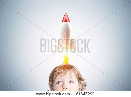 Close up of a head of an adorable little baby boy standing near a light gray wall with a rocket taking off above his head.