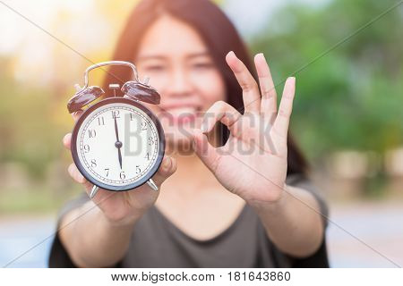 Times is OK or Right time with right job concept Asian women hand show clock times with hand show good alright sign.