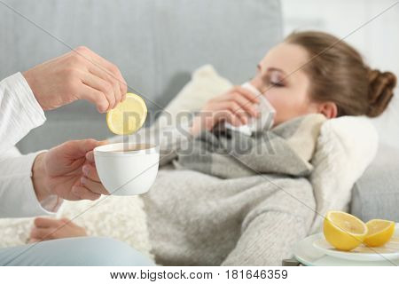 Male hands holding cup of hot drink with lemon for ill girl