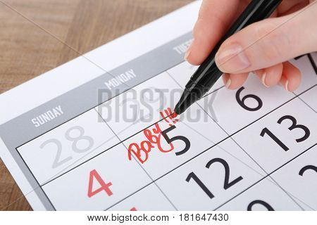 Woman writing BABY on date in calendar, close up