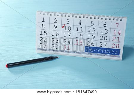 Calendar with marked date and marker on wooden background