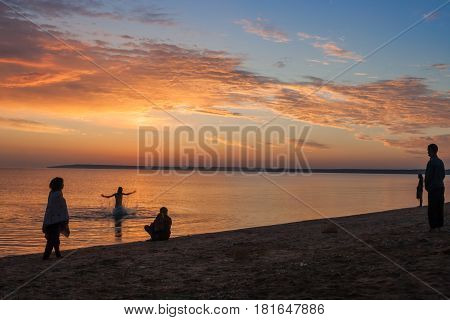 Beautiful colorful summer sea sunrise landscape with amazing colorful clouds in a blue sky and unrecognizable people silhouettes waiting for the Sun. One man is splashing and jumping in water. In Crimea, Azov sea, Ukraine 2013.