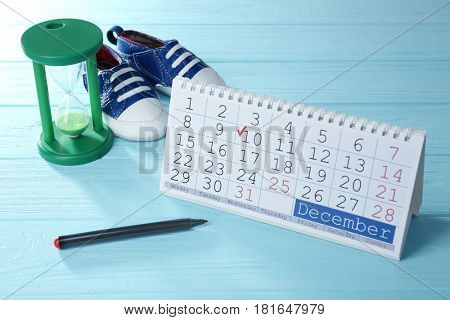 Calendar with marked date, marker, booties and hourglass on wooden background