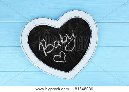 Mini chalkboard in cute form of heart with written word BABY on blue wooden background