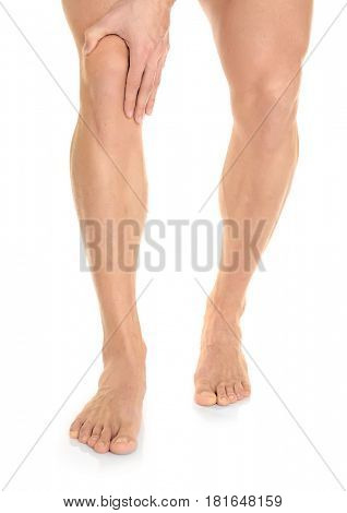 Legs of young man suffering from pain in knee on white background