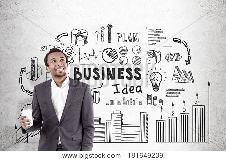 Close up portrait of a happy African American businessman holding a paper cup of coffee and standing near a concrete wall with a business idea sketch drawn on it.